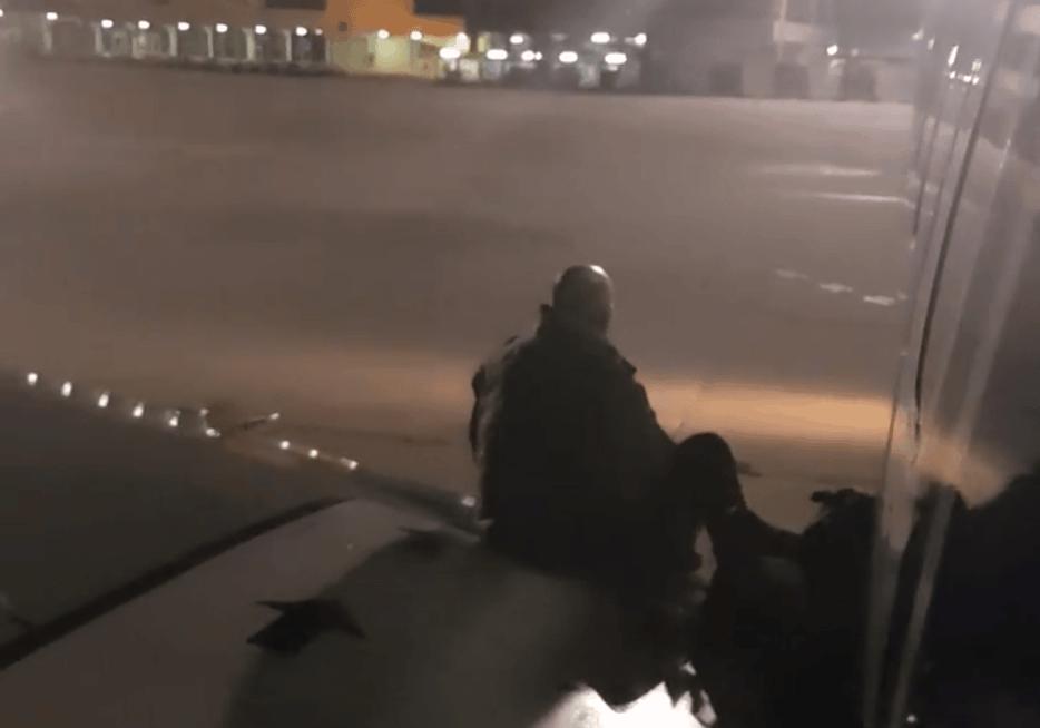 Un passager ouvre la sortie d'urgence et sort sur l'aile
