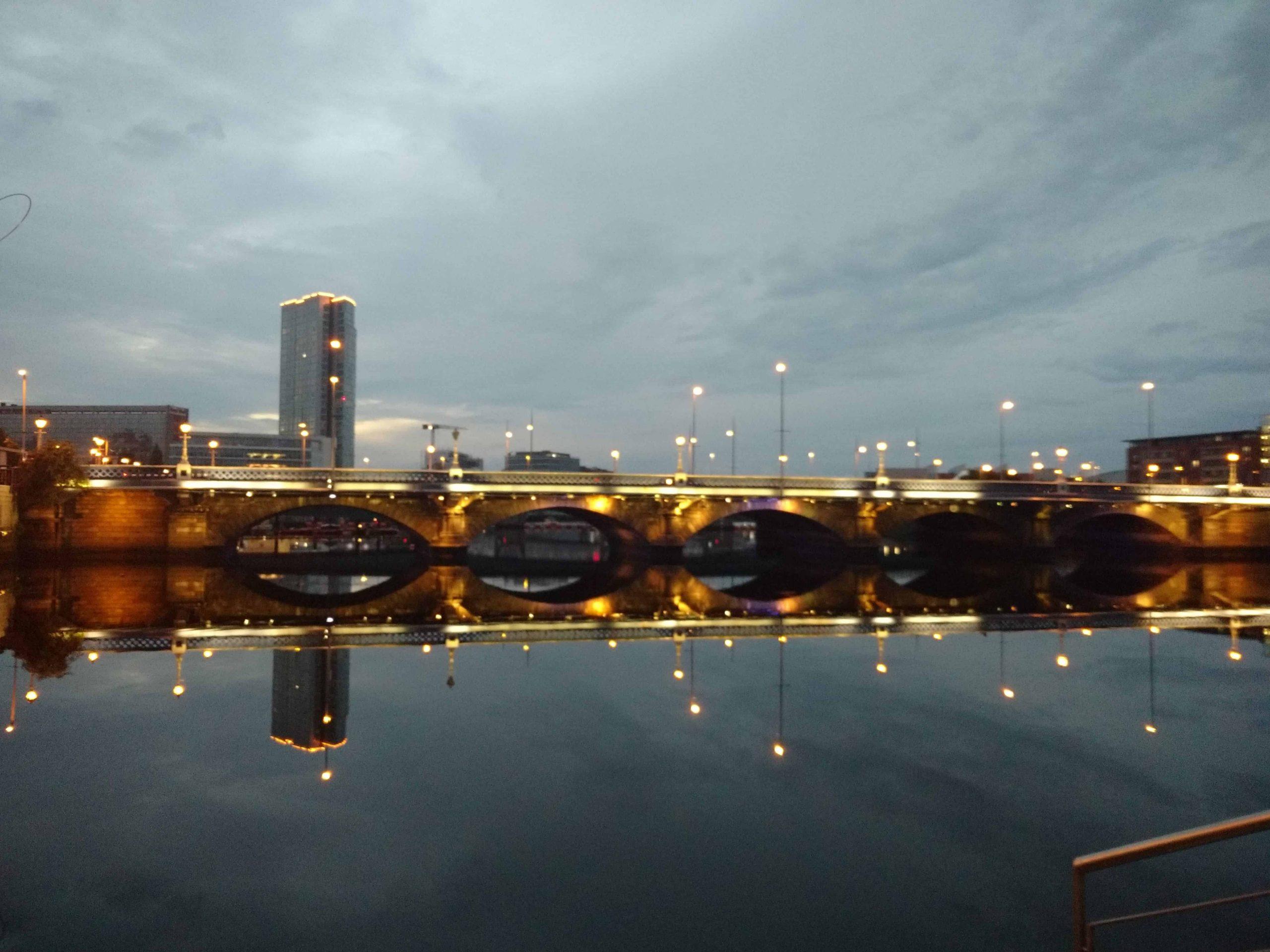 Un pont éclairé et les lumières de la ville se reflètent dans l'eau.